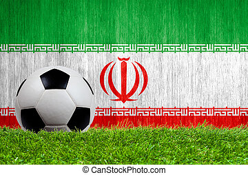 Soccer ball on grass with Iran flag background close up