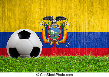 Soccer ball on grass with Ecuador flag background close up