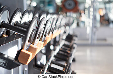 Dumb bells lined up in a fitness studio picture is short...