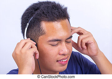 Close up of a young boy face listening to music with earphones