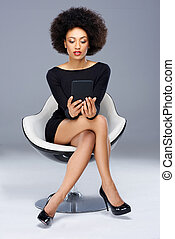 Elegant glamorous African American woman sitting in a black...