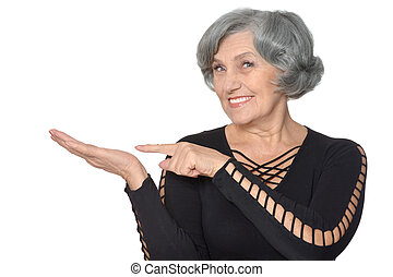 Senior woman pointing - Senior woman in black dress pointing...