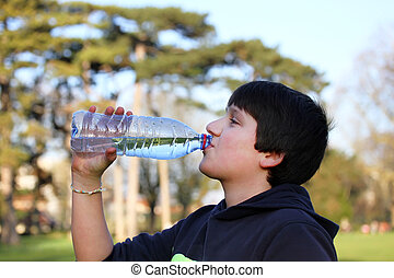 A boy thirsty eagerly drinking water from plastic bottle