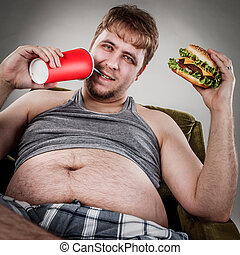 Fat man eating hamburger seated on armchair Style fast food...