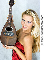 Girl with mandolin - Girl in red corset with old mandolin in...