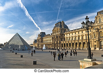 PARIS - March 20 Tourists enjoy the weather at the Louvre on...