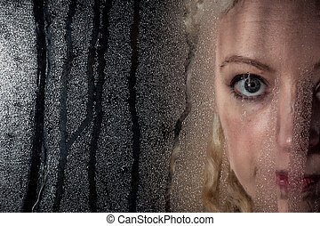 Sad woman looking through window - Sad and depressed woman...