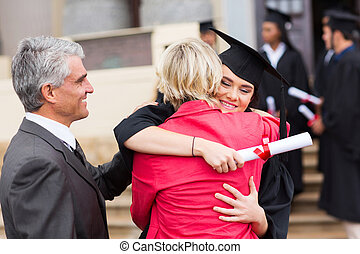 female graduate hugging her mother - happy female graduate...