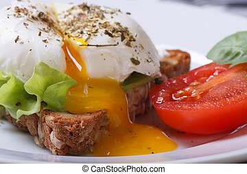open poached egg, tomato and bread on a plate macro...