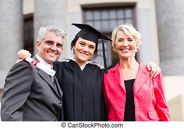 young female graduate with parents