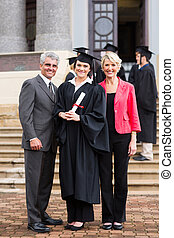 young girl graduate standing with parents - portrait of...