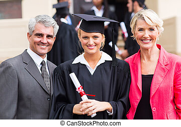 young female graduate with parents - smiling young female...