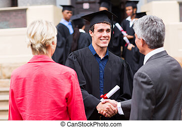 male graduate handshaking with his father