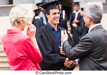 male graduate handshaking with his grandfather - cheerful...
