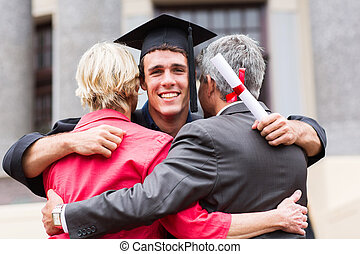 young male graduate hugging his parents - handsome young...