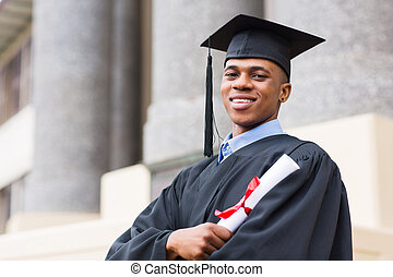 african american male graduate standing outside college -...