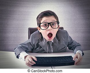 Shocked computer nerd - Shocked child nerd working with a...