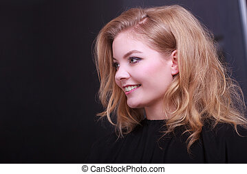 Beautiful smiling girl with blond wavy hair by hairdresser....