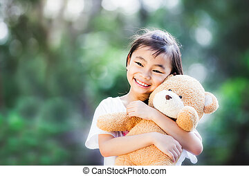 Asia little girl with doll bear in nature park