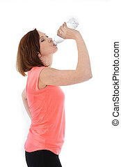 young attractive red hair sport woman drinking water in...
