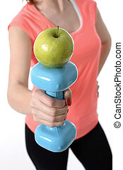 woman holding gym weight and apple in healthy nutrition concept