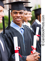 african american male graduates standing with classmates -...