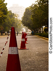 Traffic cones on road with trees - Red traffic cones on a...