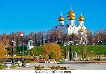 White-stone cathedral with golden domes on the hill