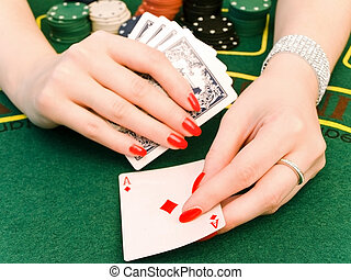 woman playing in casino - woman hand with jewelry holding...
