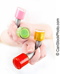 varnish - a woman holding the vials with different colors...