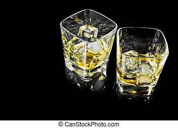 two glasses of alcoholic drink with ice on black background...