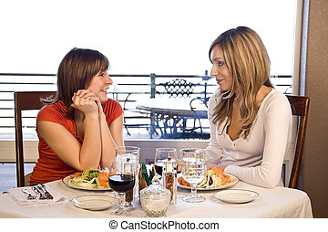 2 friends having lunch at a cafe laughing and smiling