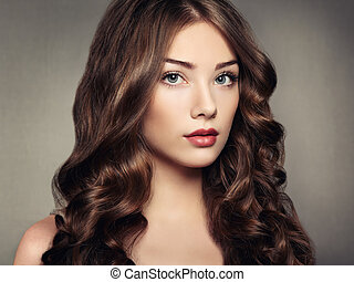 Portrait young beautiful woman with curly hair. Fashion...