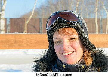 middle-aged brunette on a hillside in a cap and ski goggles...