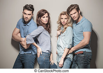 fashion models in blue jeans and casual polo shirts posing...