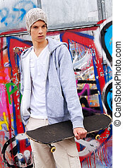 cool-looking teenager man in front of graffiti