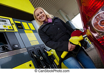 woman at the gas station to fill up - a young woman at a gas...