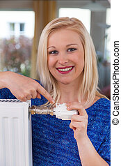 woman lowers the room temperature - to conserve energy and...