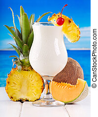 cocktail pina colada with fresh fruits on a beach