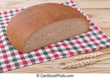Loaf of bread and wheat ears on a wooden table.