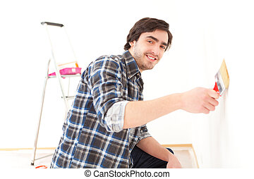Attractive young man painting a wall in his new flat - View...