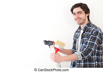 Attractive young man painting a wall in his new flat