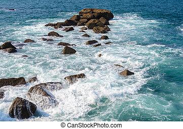 Sea water breaking on rocks