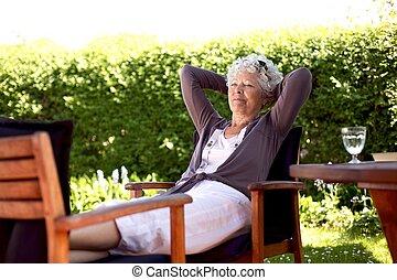 Elder woman resting in backyard garden