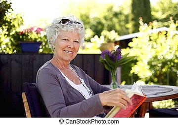 Senior woman in garden with a book
