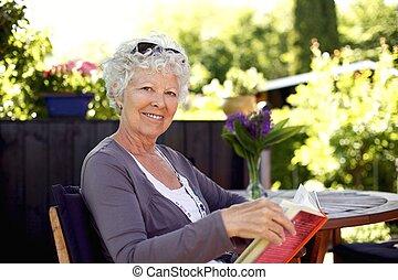 Senior woman in garden with a book