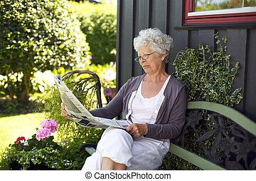 Relaxed old woman reading newspaper in her backyard -...