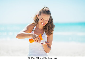 Happy young woman on beach applying sun screen creme