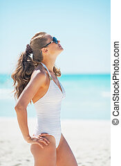 Young woman in sunglasses tanning on beach