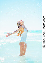 Happy young woman at seaside rejoicing
